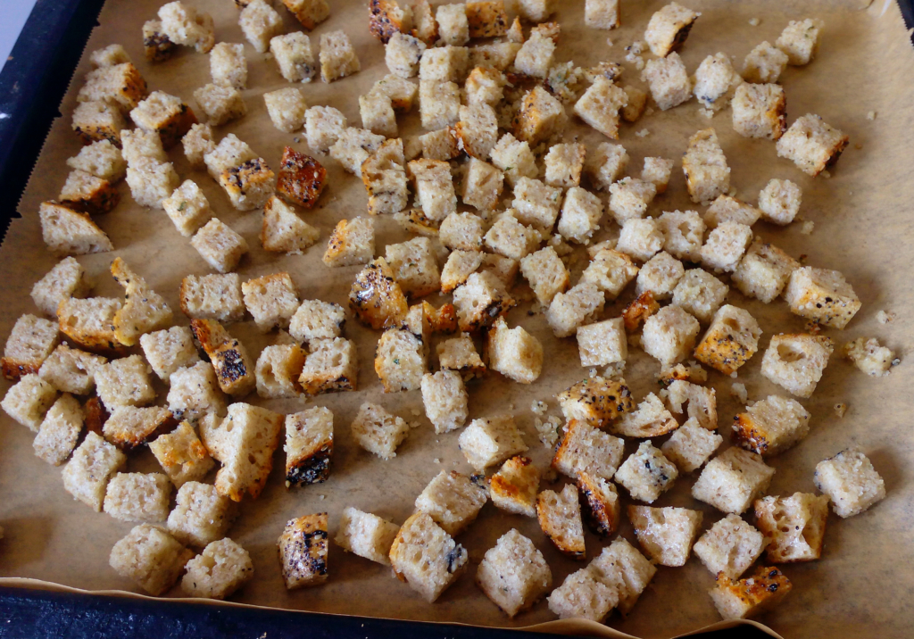 stale bread cubes seasoned and spread on a baking sheet