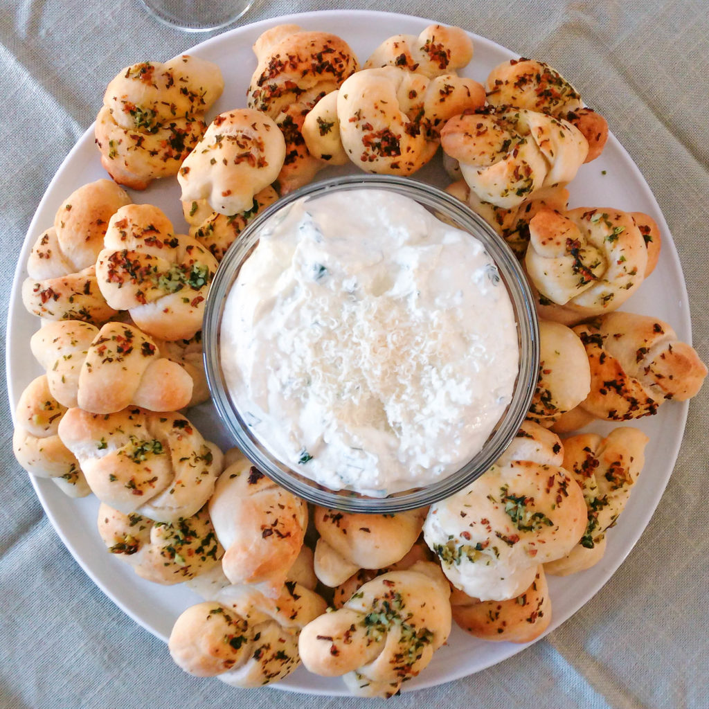 These garlic knots are so soft and chewy, especially when paired with this delicious Parmesan yogurt dip! You must try this recipe. | #garlicknots #homemadegarlicknots #pizzadough | simplyanchy.com