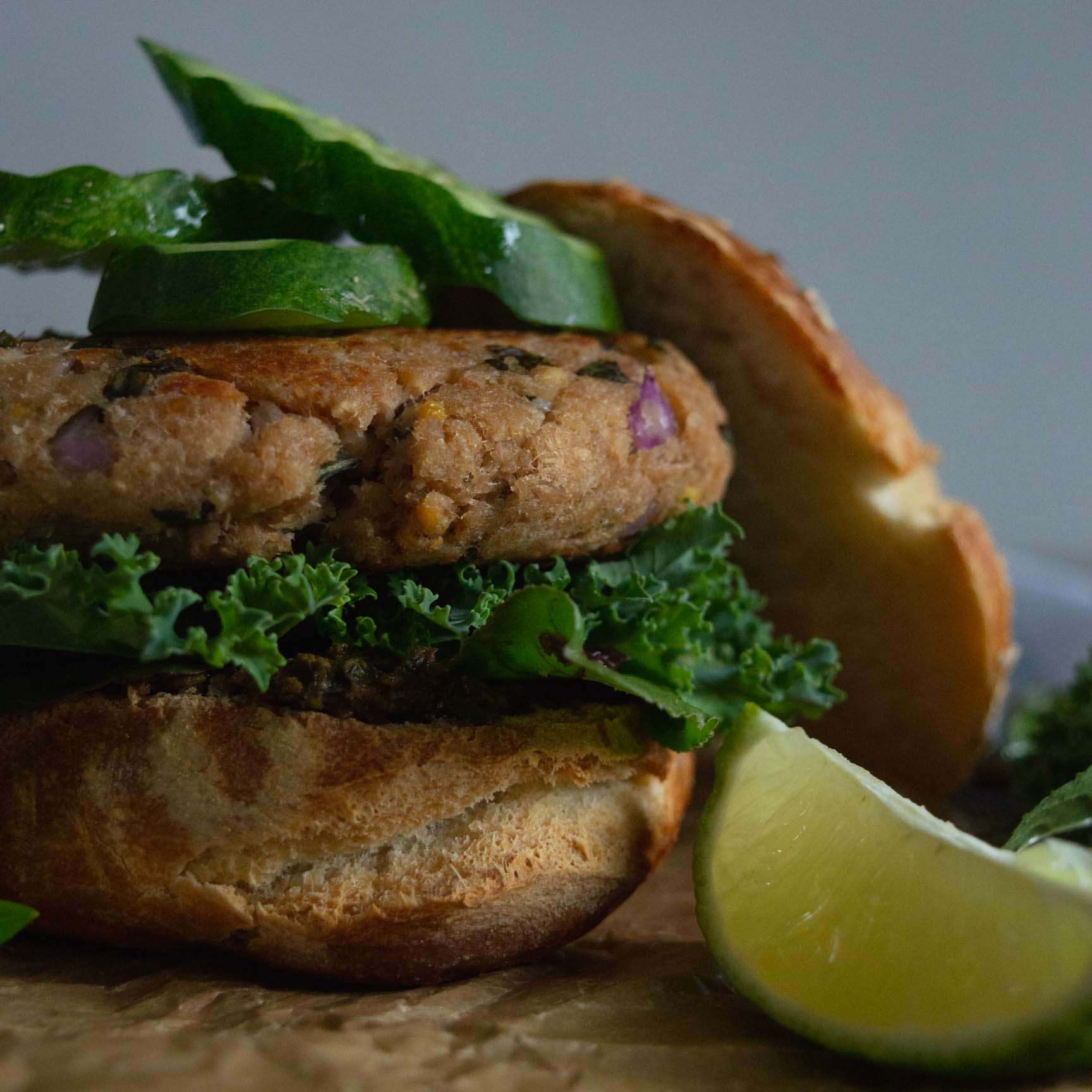 quick lime and basil tuna burger served on a bun with salad leaves and a wedge on lime