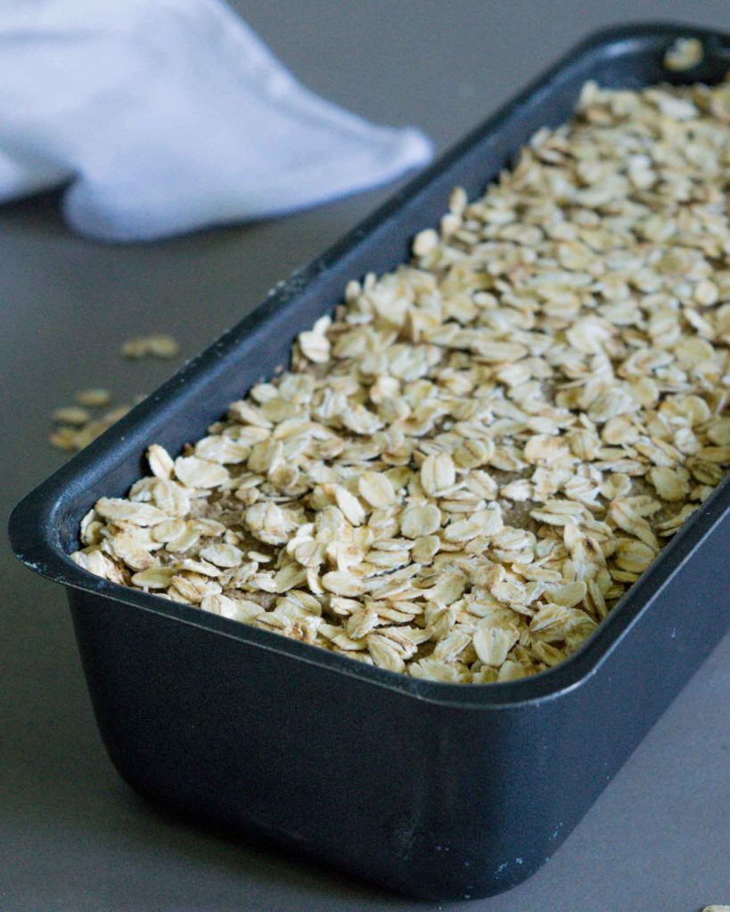 rye flour dough in a loaf tin, topped with oats
