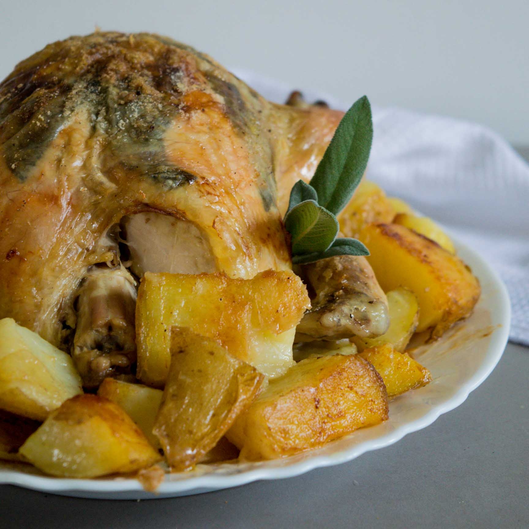 whole roasted sage chicken served on a platter with roasted potatoes