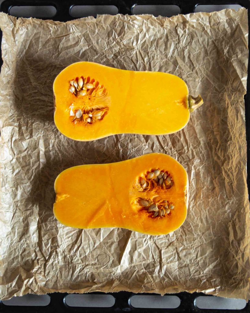 butternut squash halved and ready for roasting on baking sheet