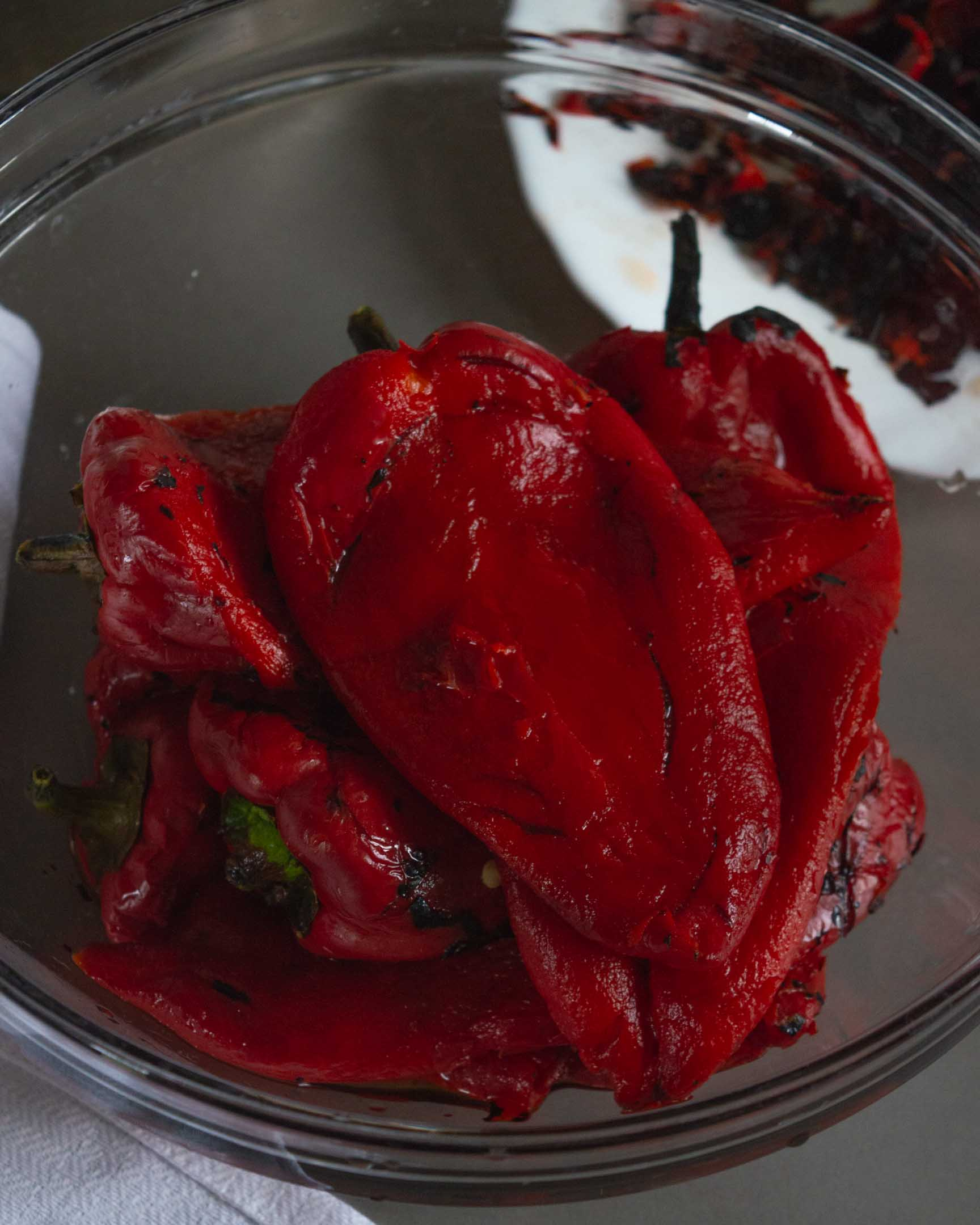 sweet red peppers, roasted and peeled, in glass bowl