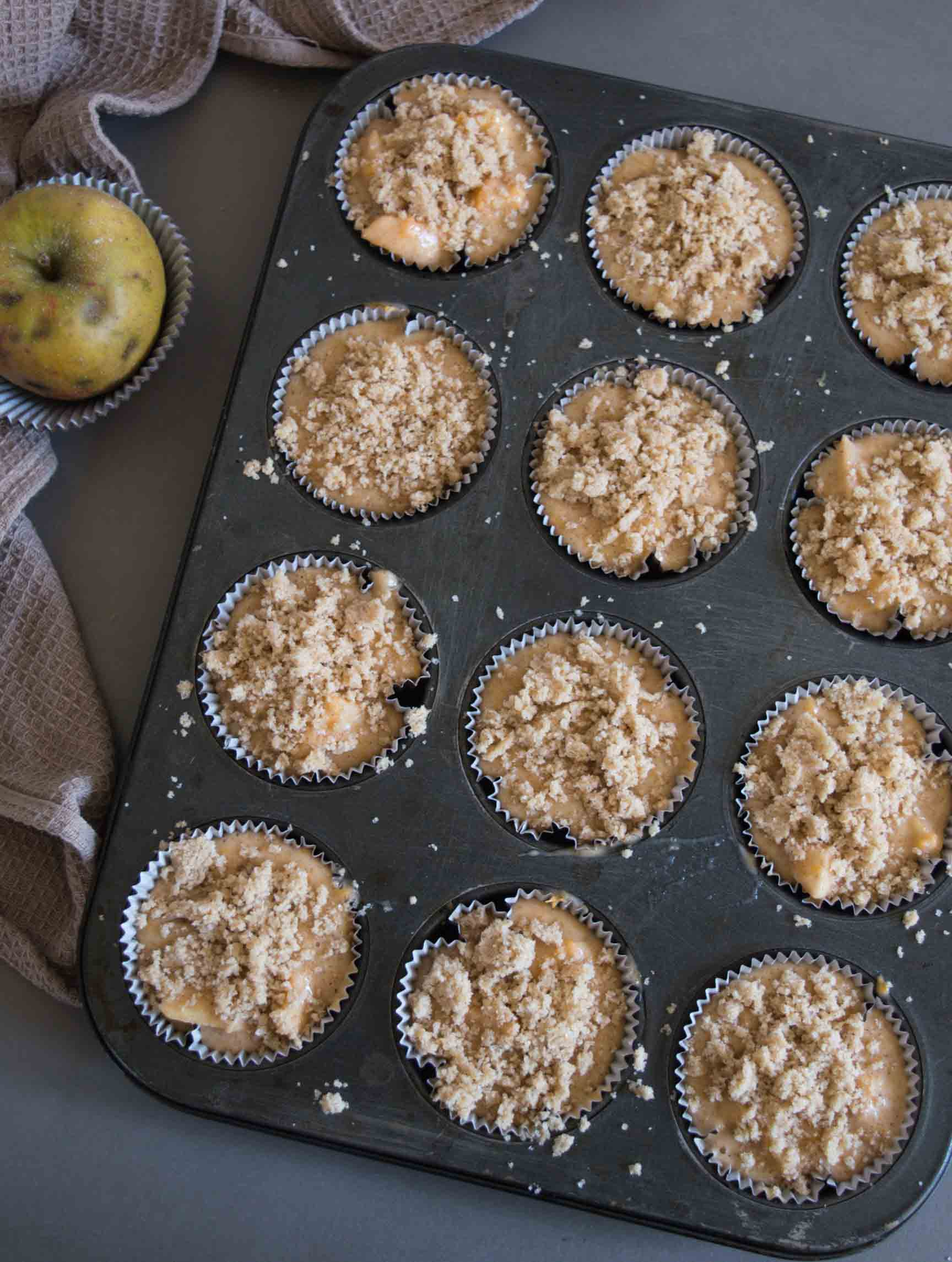 pumpkin apple muffin before baking, in muffin tin, topped with streusel
