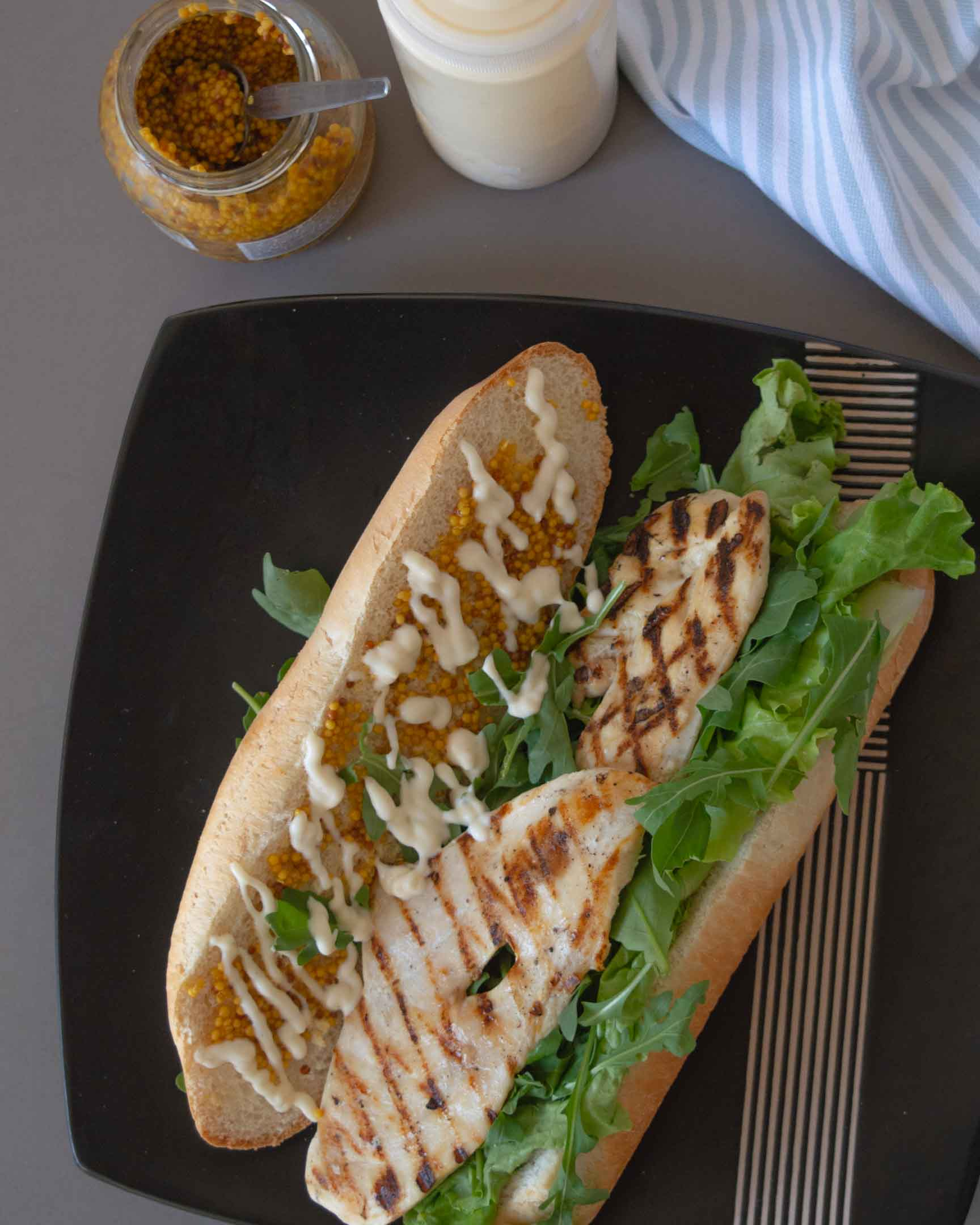 grilled chicken sandwich on a plate, from above