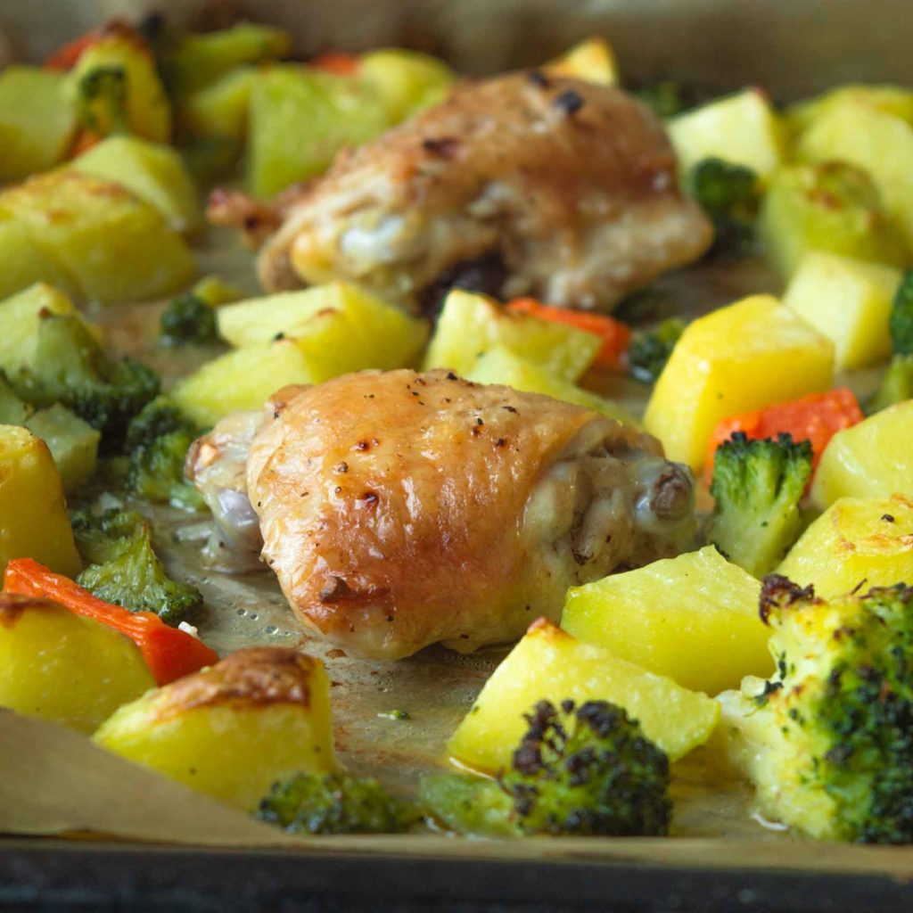 chicken thighs with broccoli and potatoes on sheet pan close up
