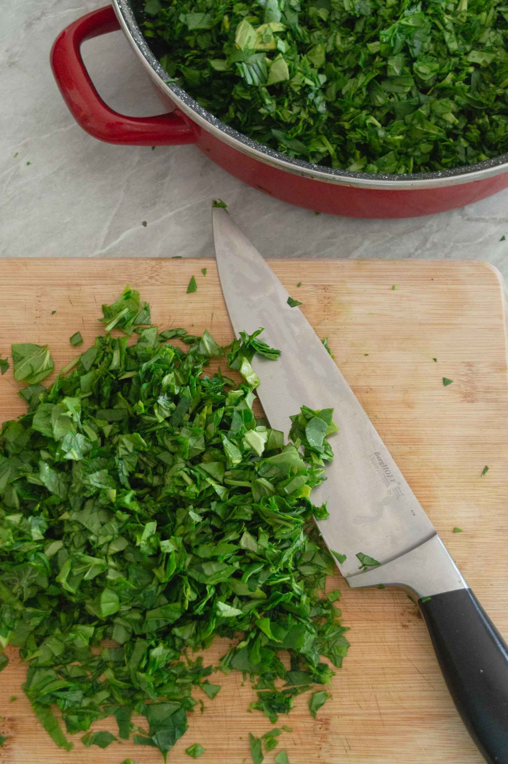 spinach leaves cut with knife on cutting board